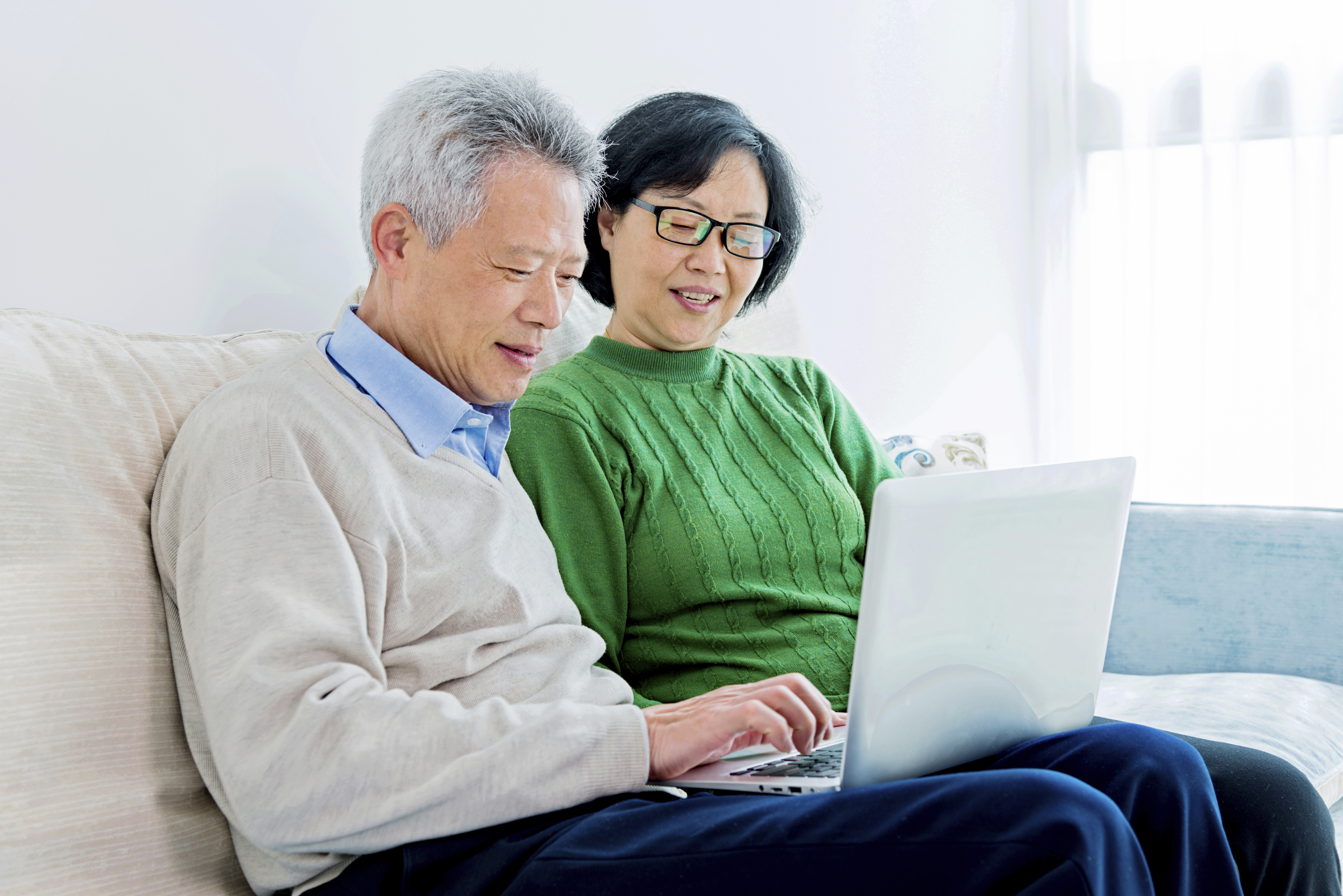 Happy senior asian couple working with laptop